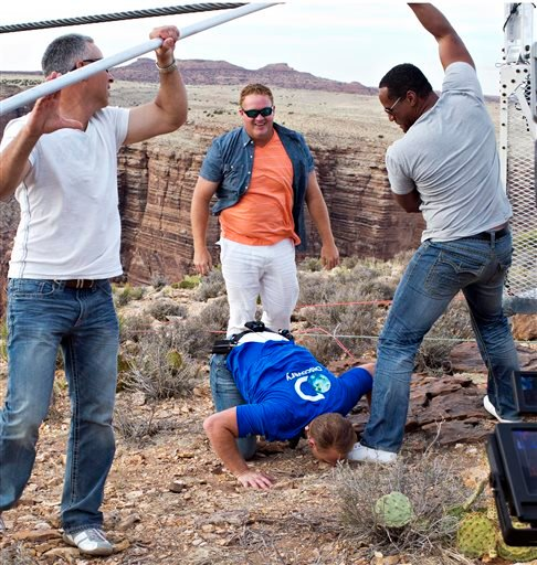 Aerialist Nik Wallenda kisses the ground after walking a 2-inch-thick steel cable that took him a quarter mile over the Little Colorado River Gorge in northeastern Arizona on Sunday, June 23, 2013.