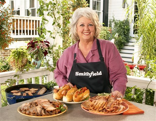 This undated image released by Smithfield Foods shows celebrity chef Paula Deen wearing a Smithfield apron as she stands in front of various Smithfield meat products.