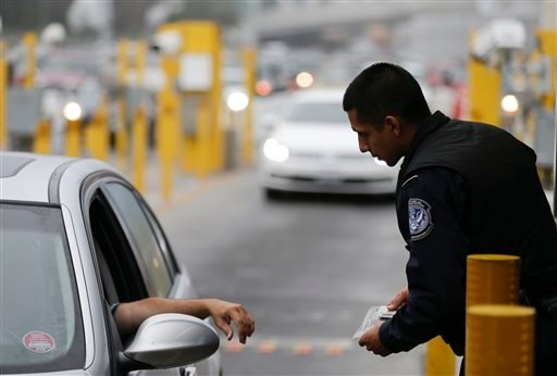 A Customs and Border Protection officer speaks to a driver in his lane at the San Ysidro port of entry Thursday, June 27, 2013, in San Diego.