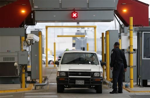 A Customs and Border Protection officer watches as a car moves through a large scanning device during a secondary inspection at the San Ysidro port of entry Thursday, June 27, 2013, in San Diego.