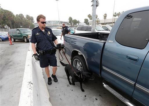 A Customs and Border Protection officer works with a canine unit among the cars in line at the San Ysidro port of entry Thursday, June 27, 2013, in San Diego.