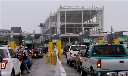 Cars wait in lines to cross at the San Ysidro port of entry Thursday, June 27, 2013, in San Diego, as construction work continues on a new building.