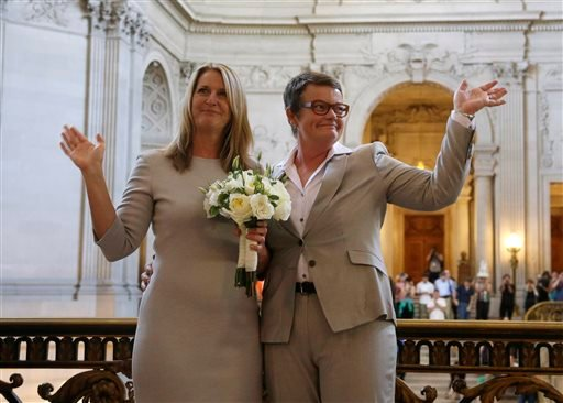 Sandy Stier, left, and Kris Perry wave at supporters after they were wed by California Attorney General Kamala Harris at City Hall in San Francisco, Friday, June 28, 2013. (AP)