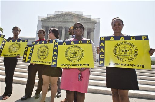 This June 25, 2013 file photo shows representatives from the NAACP Legal Defense Fund standing outside the Supreme Court in Washington, awaiting a decision in Shelby County v. Holder, a voting rights case in Alabama.