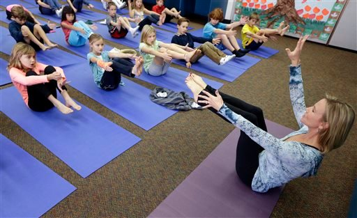 In this Dec. 11, 2012 file photo, Yoga instructor Kristen McCloskey, right, leads a class of third graders at Olivenhain Pioneer Elementary School in Encinitas, Calif.