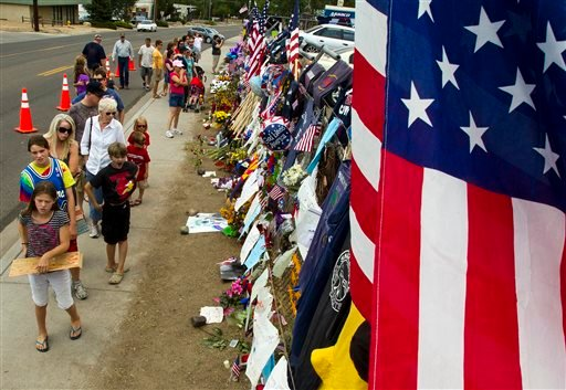 Items are displayed at a makeshift memorial at the Fire Station No. 7 memorial for fallen firefighters Saturday, July 6, 2013, in Prescott, Ariz.