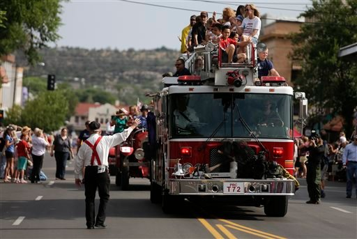 A fire truck carrying friends and family members of the Granite Mountain Interagency Hotshot Crew leads the Prescott Frontier Days Rodeo Parade Saturday, July 6, 2013 in Prescott, Ariz.