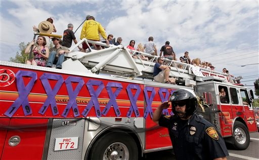 Prescott Police Officer Todd Attenberger salutes as a fire truck carrying friends and family members of the Granite Mountain Interagency Hotshot Crew lead the Prescott Frontier Days Rodeo Parade Saturday, July 6, 2013 in Prescott, Ariz.