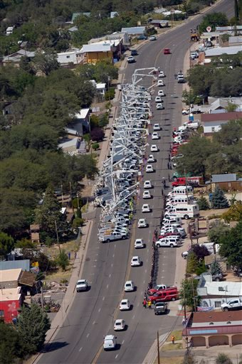 A procession of 19 hearses drives by, Sunday, July 7, 2013, in Yarnell, Ariz, The elite crew of firefighters were overtaken by the out-of-control blaze as they tried to protect themselves from the flames under fire-resistant shields last Sunday.