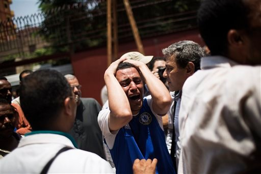 An Egyptian man cries outside a morgue after carrying the corpse of his brother killed near the Republican Guard building in Cairo, Egypt, Monday, July 8, 2013.