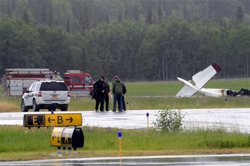 Investigators look at the remains of a fixed-wing aircraft that was engulfed in flames Sunday July 7, 2013 at the Soldotna Airport in Soldotna, Alaska.