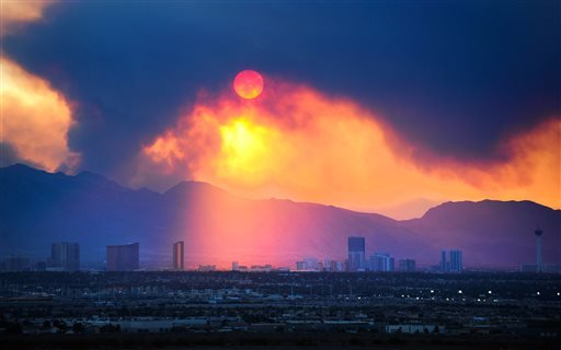 The Las Vegas Strip skyline is seen as smoke continues to billow from the Carpenter 1 fire on Mount Charleston on Monday, July 8, 2013 in Las Vegas.