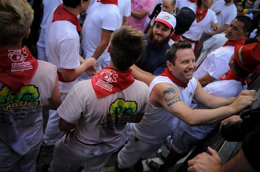 A reveler with a tattoo of a bull on his right arm, smiles as he waits on the Estafeta corner for the second running of the bulls at the San Fermin fiestas, in Pamplona northern Spain on Monday, July 8, 2013.