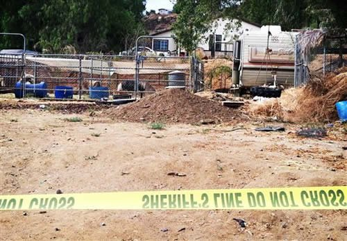 Crime scene tape cordons off an area where Riverside County Sheriff's Deputies are investigating reports of human remains on Wednesday, July 10, 2013 in Menifee, Calif.
