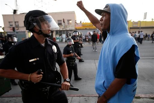 A protester confronts a Los Angles police officer during a demonstration in reaction to the acquittal of neighborhood watch volunteer George Zimmerman on Monday, July 15, 2013, in Los Angeles.