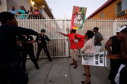 Protesters confront Los Angles police officers during a demonstration in reaction to the acquittal of neighborhood watch volunteer George Zimmerman on Monday, July 15, 2013, in Los Angeles.