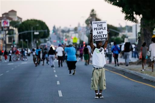 A protester holds up a sign while marching down the street during a demonstration in reaction to the acquittal of neighborhood watch volunteer George Zimmerman on Monday, July 15, 2013, in Los Angeles.