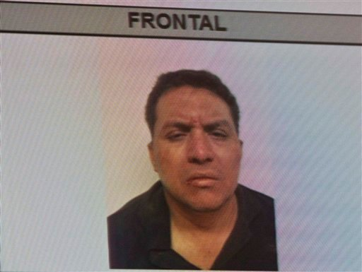 A mugshot of the Zetas drug cartel leader Miguel Angel Trevino Morales is shown on a TV screen during a news conference given by the Mexican government in Mexico City, Monday, July 15, 2013.