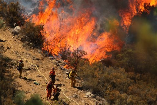 A female inmate hand crew from Puerta La Cruz and firefighters in an engine company with them set fire to reinforce the line to stave off part of the Mountain Fire Tuesday, July 16, 2013. (AP Photo/The Desert Sun, Crystal Chatham)