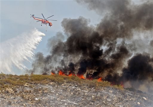 Helicopter crews work the Mountain Fire as it burns in the wilderness near Lake Hemet, Calif. Tuesday, July 17th, 2013. (AP Photo/The Desert Sun, Jay Calderon)