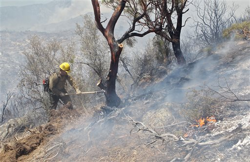 A member of the Big Bear Hot Shots works the fire line on Apple Valley Rd. near Lake Hemet, Calif. Tuesday, July 17th, 2013. (AP Photo/The Desert Sun, Jay Calderon)