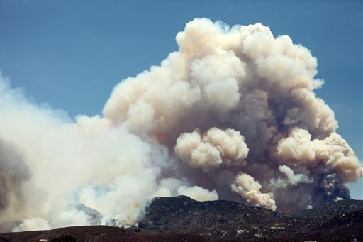Smoke from the Mountain Fire rises as seen from Lake Hemet, Calif. on Tuesday, July 16, 2013, in Lake Hemet, Calif. (AP Photo/The Desert Sun, Marilyn Chung)