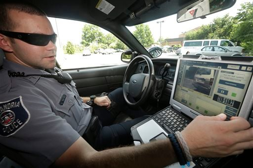Officer Dennis Vafier, of the Alexandria Police Department, uses a laptop in his squad car to scan vehicle license plates during his patrols, Tuesday, July 16, 2013, in Alexandria, Va. (P)