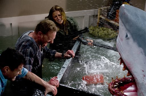 "In this image released by Syfy, Ian Ziering, second left, and Cassie Scerbo battle a shark in the Syfy original film ""Sharknado."""