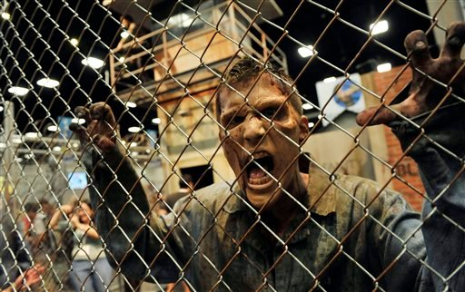 """A zombie character in an exhibit inspired by the television series """"The Walking Dead"""" screams at onlookers during the Preview Night event on Day 1 of the 2013 Comic-Con International Convention on Wednesday, July 17, 2013 in San Diego, Calif. (AP)"""