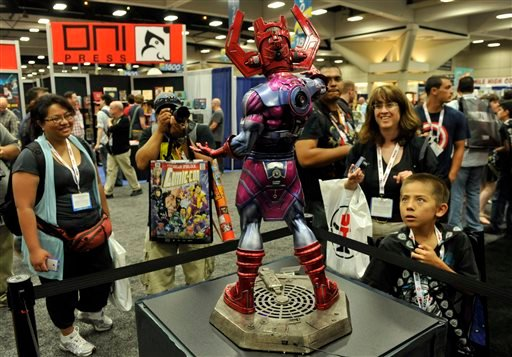 """Comic-Con attendees look at a """"Galactus"""" model during the Preview Night event on Day 1 of the 2013 Comic-Con International Convention on Wednesday, July 17, 2013 in San Diego, Calif. (Photo by Chris Pizzello/Invision/AP)"""