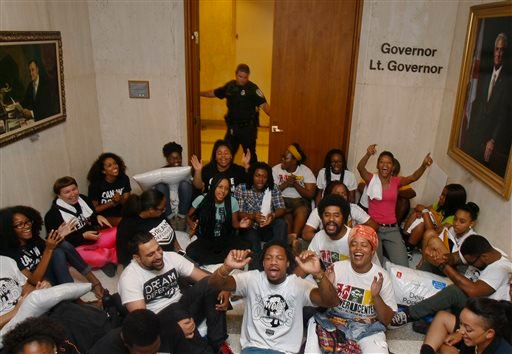 A Capitol Police officer shuts the doors to Florida Gov. Rick Scott's office at 5 p.m. Wednesday July 17, 2013 as protestors chant in the Capitol in Tallahassee, Fla. (AP)