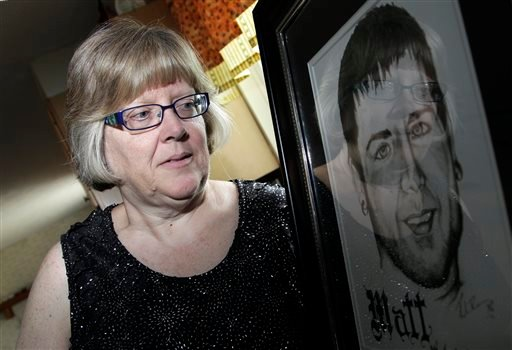 Jerri Jackson, mother of Aurora, Colo. theater shooting victim Matthew McQuinn, stands next to a sketch of her son in Springfield, Ohio on Sunday, July 14, 2013.