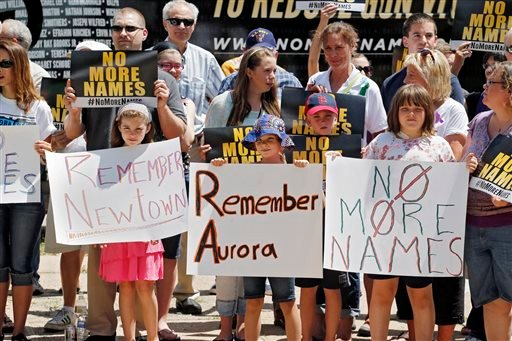 People hold signs as they gather for a remembrance rally for the anniversary of the Aurora theater shooting at Cherry Creek State Park in Aurora, Colo., Friday, July 19, 2013. (AP)