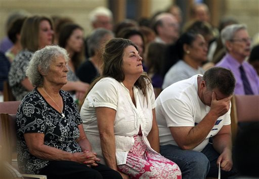 The grandmother, left, mother, and father of Aurora movie theater shooting victim Micayla Medek mourn during a memorial mass held for families and supporters of those killed Friday July 19, 2013. (AP Photo/Brennan Linsley)