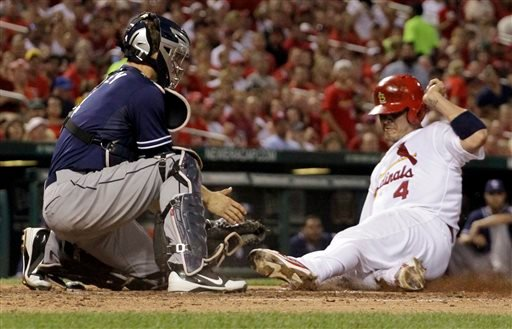 San Diego Padres catcher Nick Hundley, left, prepares to tag St. Louis Cardinals' Yadier Molina out at home during the sixth inning of a baseball game on Friday, July 19, 2013, in St. Louis. (AP Photo/Jeff Roberson)