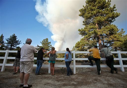 In this Friday, July 19, 2013, photo, Pine Cove, Calif. residents watch smoke rise from a wildfire near Idyllwild, Calif. The human-caused fire, which began Monday, has burned structures and forced evacuations. (AP Photo/The Desert Sun, Richard Lui)