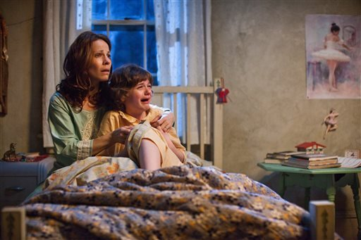 "In this publicity image released by Warner Bros. Pictures, Lili Taylor portrays Carolyn Perron, left, and Joey King portrays Christine in a scene from ""The Conjuring."" (AP Photo/New Line Cinema/Warner Bros. Pictures, Michael Tackett)"