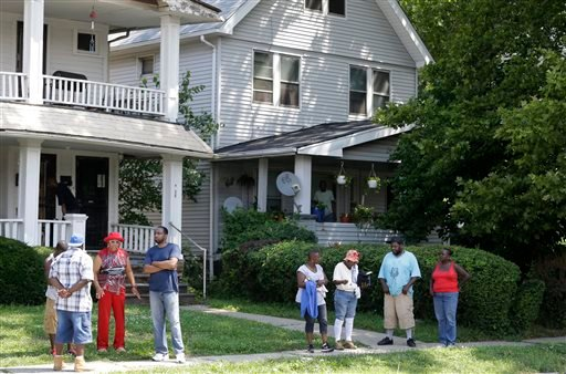 East Cleveland residents watch the scene Sunday, July 21, 2013, close to where three bodies were recently found in East Cleveland, Ohio.