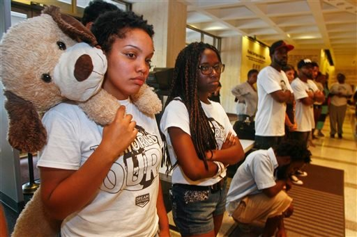 "Dream Defenders President Melanie Andrade, holding ""Wilson,"" a teddy doggie and Regina Joseph listen to a speaker outside Florida Gov. Rick Scott's office after it was closed for the evening Friday, July 19, 2013 at the Capitol in Tallahassee, Fla."