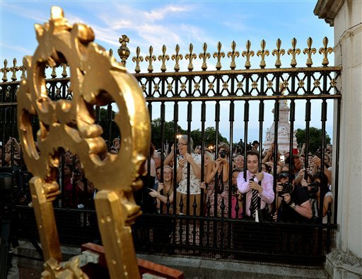 The large waiting crowds cheers as they read the news on an easel in the forecourt of Buckingham Palace.