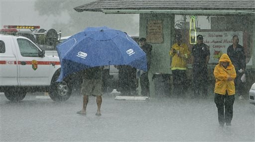 Firefighters take cover at Lake Hemet Market as Louie Delegge walks around under his sun shade in the heavy rains on Sunday, July 21, 2013. (AP Photo/The Press-Enterprise, Terry Pierson)