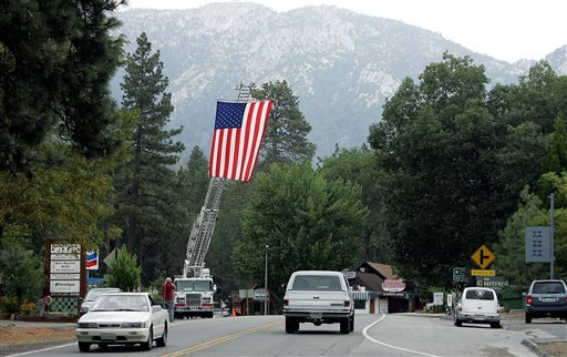 A ladder truck flies the American flag to greet residents back to Idyllwild after the evacuation order was rescinded Sunday, July 21, 2013, in the areas affected by the Mountain Fire. (AP Photo/The Press-Enterprise, Terry Pierson)