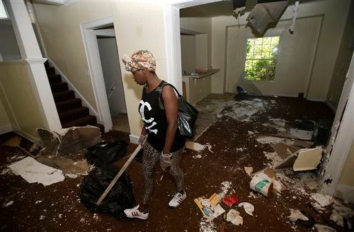 Sanautica Hicks-Ross, 18, searches an abandoned home Sunday, July 21, 2013, near where three bodies were found in East Cleveland, Ohio.