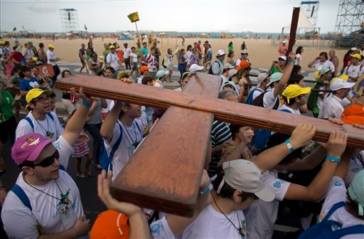 A wooden cross, symbol of the World Youth Day given to young people of the church in 1983 by Pope John Paul II, is carried along Copacabana beach by pilgrims in Rio de Janeiro, Brazil, Sunday July 21, 2013.