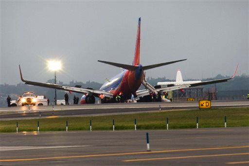 A southwest airlines plane rests on the tarmac after what officials say was a nose gear collapse during a landing at LaGuardia Airport, Monday, July 22, 2013, in New York. The Federal Aviation Administration says the plane landed safely. (AP Photo)