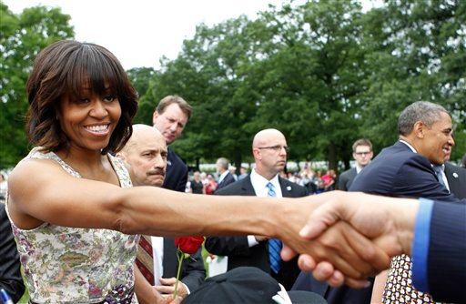 In this May 27, 2013 file photo, President Barack Obama and first lady Michelle Obama greet visitors to Section 60 on Memorial Day at Arlington National Cemetery in Arlington, Va.