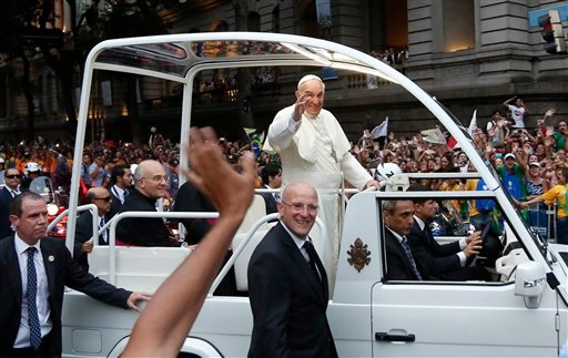 Pope Francis waves from his popemobile as he makes his way into central Rio de Janeiro, Brazil, Monday, July 22, 2013.