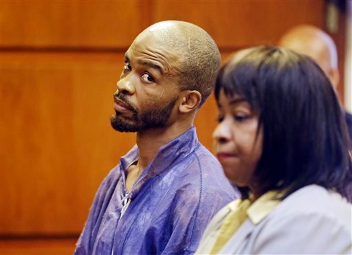 Michael Madison glances at court-appointed attorney Marlene Rideenour during his arraignment in East Cleveland on Monday, July 22, 2013. (AP Photo/Mark Duncan)