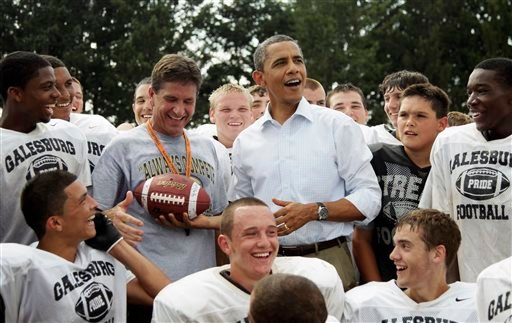 In this Aug. 17, 2011 file photo, President Barack Obama reacts to catching a football tossed to him as he visits the Galesburg High School football team in Galesburg, Ill. (AP Photo/Carolyn Kaster, File)