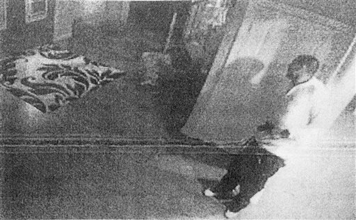 This black and white photo taken from former New England Patriot Aaron Hernandez's home surveillance system in North Attleborough, Mass shows Hernandez holding what authorities said appears to be a gun, shortly after Odin Lloyd was shot to death. (AP)